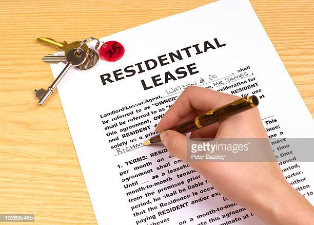 signing residential lease - lease agreement stock pictures, royalty-free photos & images