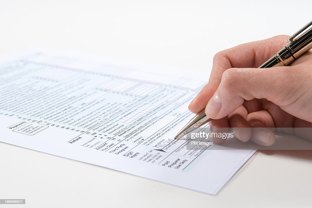 Signing tax form : Stock Photo