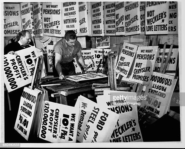 Signmakers Stanley Sawicki and Stanley Palka prepare several thousand picket signs for a possible Chrysler auto workers' strike over employee...