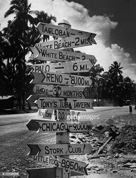 Signpost at a crossroads in Tacloban on Leyte points the way, in various systems of measurement, to American GIs' most-missed home towns and hot...