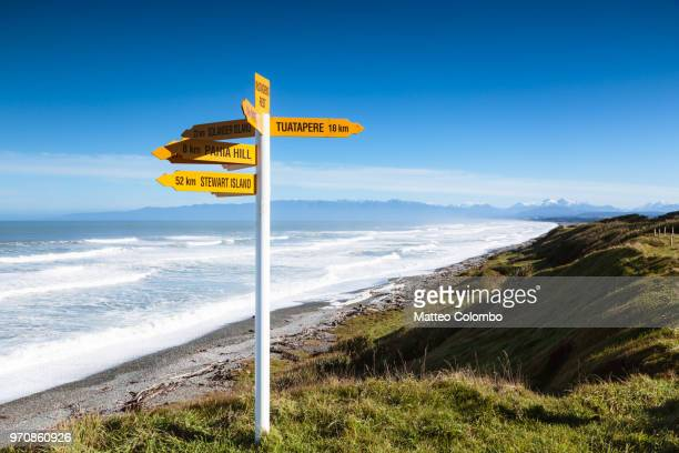 signpost near the coastline, south island, new zealand - south island new zealand stock pictures, royalty-free photos & images
