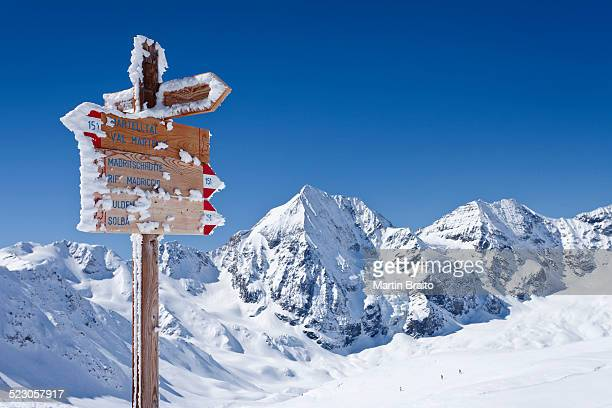 Signpost on Madritschjoch ridge, Sulden in winter, Monte Zebru mountain and Koenigsspitze mountain at the back, province of Bolzano-Bozen, Italy, Europe