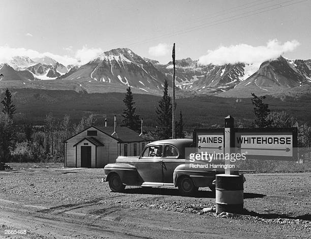 A signpost on the Alaska highway in Alaska gives rudimentary directions to the driver of a Ford twodoor coupe sedan The Dezadeash mountain range...