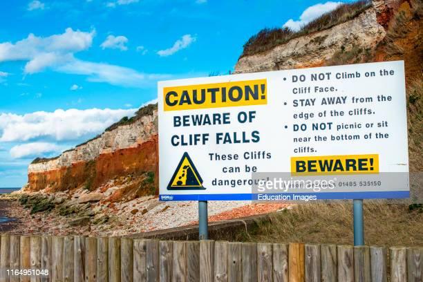 Signpost warning of coastal erosion at Hunstanton cliffs North coast England UK
