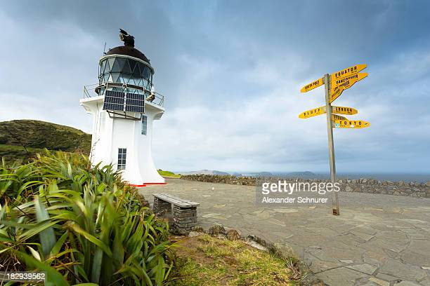 Signpost with distances and lighthouse at Cape Reinga, Cape Reinga, Northland Region, New Zealand