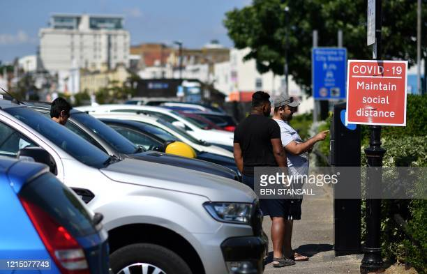 "Signs advise beachgoers arriving at the seafront to 'Maintain Social Distance due to COVID-19"", at a carpark in Southend-on-Sea, south east England..."