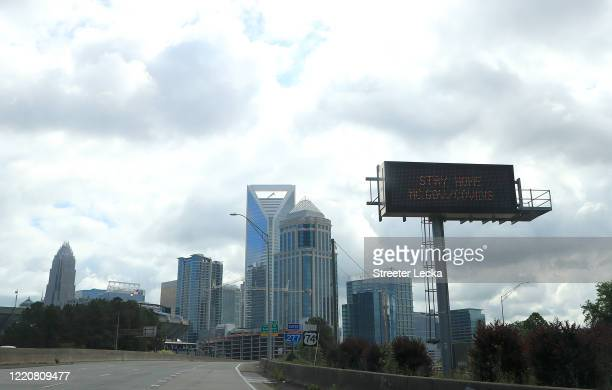 Signs along the city highways in Charlotte caution people to stay at home during the coronavirus pandemic on April 24, 2020 in Charlotte, North...