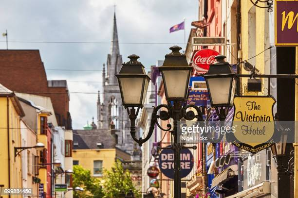 signs and lights in a street scene in downtown cork, with holy trinity church in the background, ireland. - cork city stock pictures, royalty-free photos & images