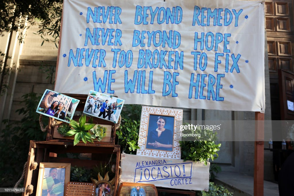 Signs and photographs sit on display outside an event for Alexandria Ocasio-Cortez, Democratic U.S. Representative candidate from New York, at the First Unitarian Church of Los Angeles in Los Angeles, California, U.S., on Friday, Aug. 3, 2018. Ocasio-Cortez campaigned on abolishing ICE en route to her stunning upset primary victory in a New York City district against a top House Democrat. Photographer: Dania Maxwell/Bloomberg via Getty Images