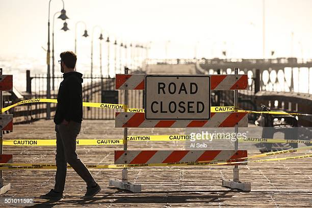 Signs and yellow tape keep spectators off the damaged Ventura Pier which was closed Friday morning as high surf pounded coastal areas and flooded...