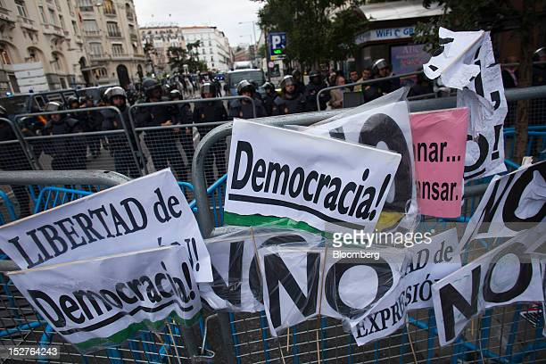 Signs are displayed on police barricades at the entrance to the Spanish parliament building during a demonstration to protest against the...