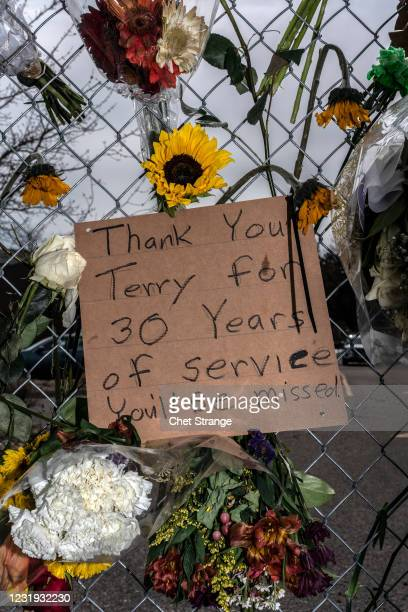 Signs are placed at a makeshift memorial for the victims of the shooting at a King Soopers grocery store on March 25, 2021 in Boulder, Colorado. The...