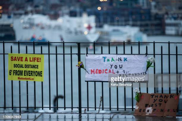 Signs are placed on fence as the USNS Comfort navy hospital ship is docked at Pier 90 in Manhattan on April 3 2020 as seen from West New York New...