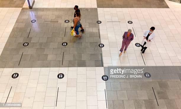 Signs are placed on the floors to direct traffic and observe social distancing guidelines inside the Westfield Santa Anita shopping mall in Arcadia,...