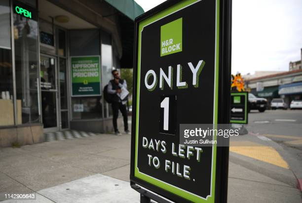 Signs are posted in front of an HR Block tax preparation office on April 15 2019 in Oakland California April 15 is the deadline in the United States...