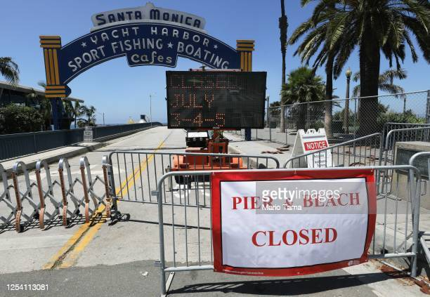 Signs are posted in front of the closed Santa Monica Pier amid the COVID-19 pandemic on July 3, 2020 in Santa Monica, California. Los Angeles County...