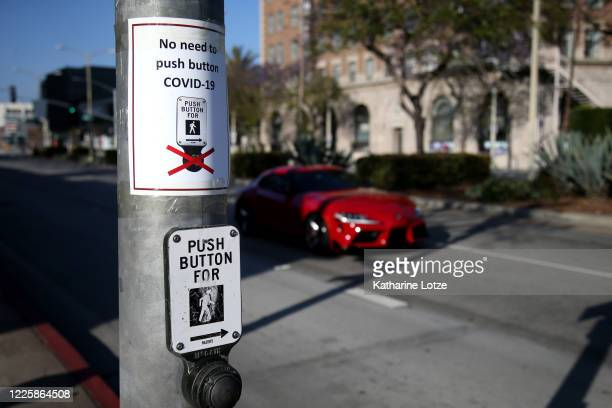 Signs are seen posted above crosswalk buttons informing pedestrians not to push the button on May 11 2020 in Culver City California Cities across Los...