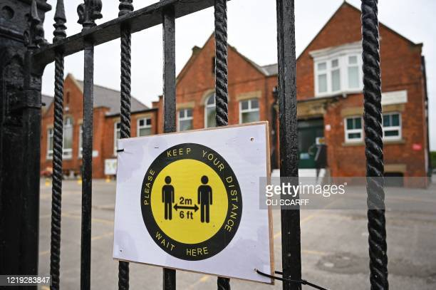 Signs ask parents and carers of school childre to to adhere to the British government's current social distancing guidelines and stay two meters...