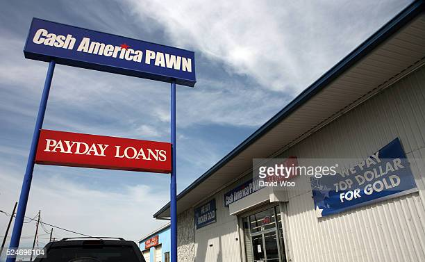 Signs at a Cash America pawn shop advertise payday loans and gold purchasing
