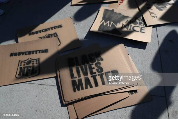 Signs calling for an NFL boycott lay at the feet of demonstrators protesting police violence before the game between the Baltimore Ravens and...