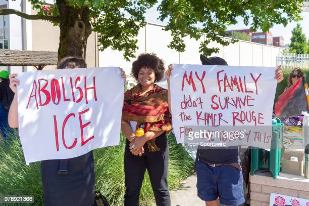 Signs demanding to abolish ICE and a sign of reminding the ordeal of refugees under Khmer Rouge regime in Cambodia are displayed at OccupyICEPDX just...