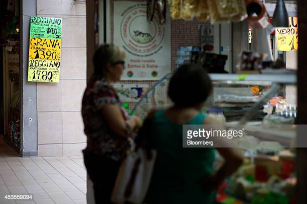 Signs displays the price in euros of Italian Reggiano Parmigiano and Grana Padano cheese as customers wait to be served at a delicatessen inside an...
