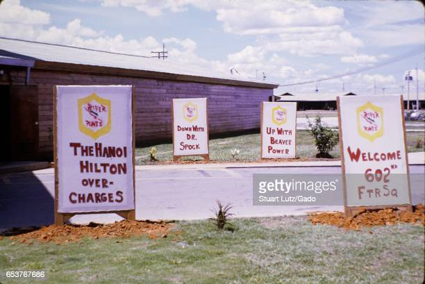 Signs erected by United States Army soldiers at Nha Trang Air Base in Vietnam during the Vietnam War including a sign reading The Hanoi Hilton...
