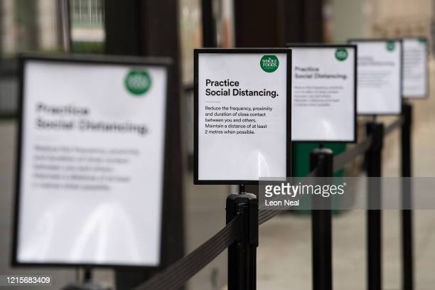 Signs explaining the need for social distancing while queueing are seen outside a branch of the Whole Foods health store on March 30, 2020 in London,...