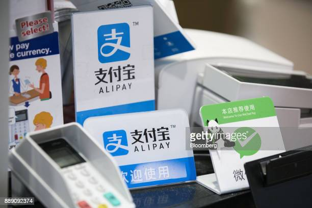 Signs for Ant Financial Services Group's Alipay an affiliate of Alibaba Group Holding Ltd center top and center bottom and Tencent Holdings Ltd's...