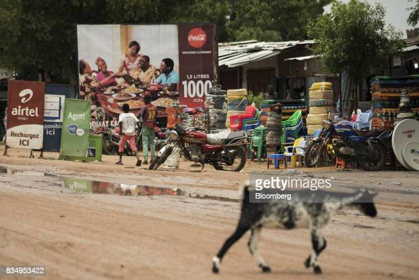 Signs for telecoms companies including Bharti Airtel Ltd and Tigo sit on a roadside near a CocaCola Co advertisement and household goods stores in...