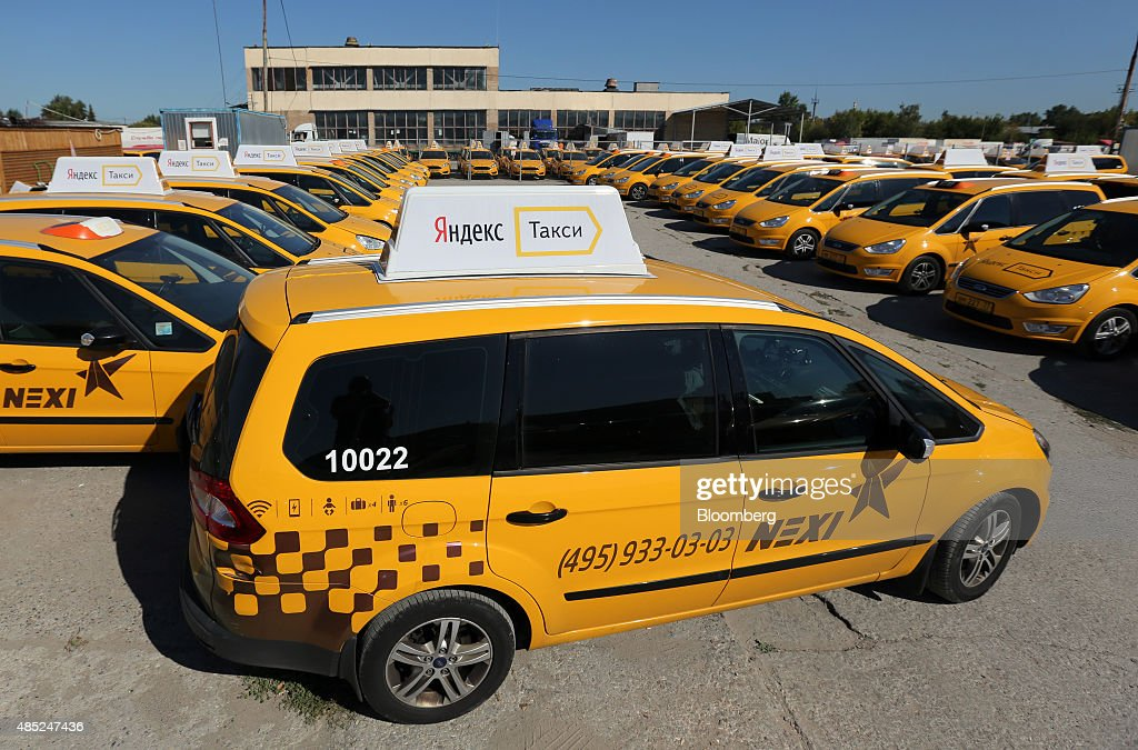 Signs for the Yandex Taxi online booking service sit on taxi