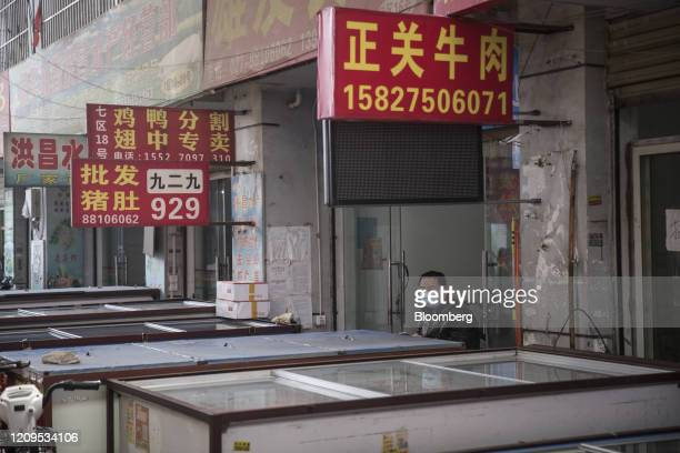 Signs for various beef, pork and poultry products are displayed at stalls as chest refrigerators stand at the Baishazhou wet market in Wuhan, Hubei...