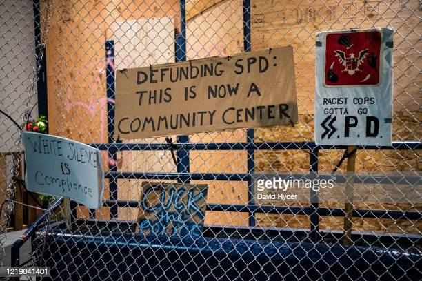 Signs hang on the exterior of the Seattle Police Departments East Precinct on June 9, 2020 in Seattle, Washington. Protests have continued in many...