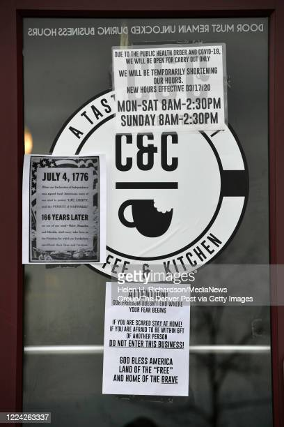 Signs hang on the side door of the CC Coffee Kitchen on May 11 2020 in Castle Rock Colorado The cafe decided to open to the general public and...