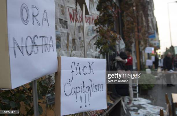 Signs in front of a shop with blockedout windows read 'Ora nostra' and 'Fuck capitalism' in the borough of Kreuzberg in Berlin Germany 18 October...