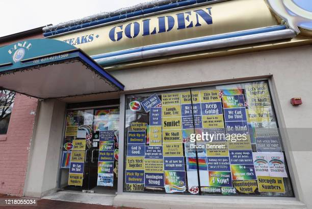 Signs in the front window of the closed Golden Dolphin Diner display messages of hope on April 10, 2020 in Huntington, New York. According to Johns...