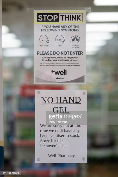 Signs in the window of a pharmacy asking people not to enter if they have symptoms of coronavirus and informing that there is no hand sanitiser in...