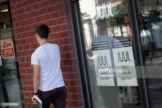 Signs in the window of the Smoke Depot advertise electronic cigarettes and pods by Juul, the nation's largest maker of e-cigarette products, on...