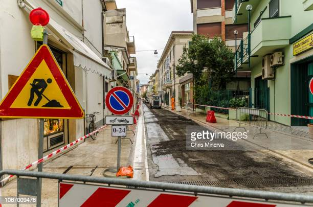 signs indicating men at work and no parking tow away zone on street being repaved - only men stockfoto's en -beelden
