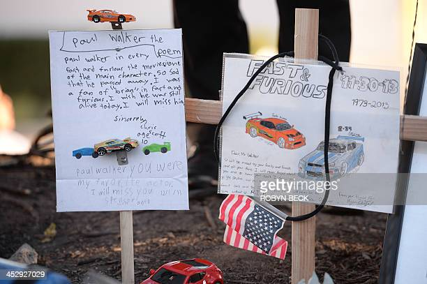 Signs left by young fans pay stand at the site of the car accident in which actor Paul Walker was killed in Santa Clarita California on December 1...