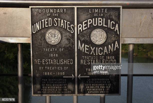 Signs mark the boundary between the Unites States and Mexico over the Rio Grande River August 6 2008 near Laredo Texas Thousands of US Border Patrol...