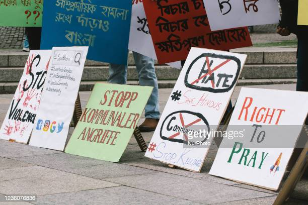 """Signs of """"stop communal violence"""" is seen during the protest over Bangladesh attack against Hindus in front of Dom Cathedral in Cologne,..."""