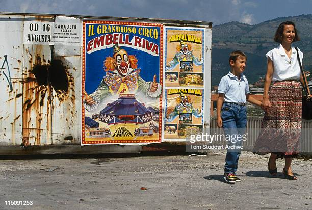 Signs Of The Times A mother and her son walk past a poster advertising a circus carries the smiling face of a clown on a shell damaged wall during...