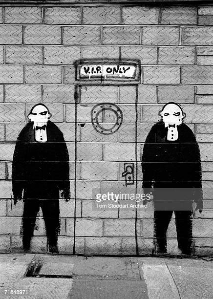 Signs Of The Times - Humourous graffiti painted on a wall in central London illustrates doormen outside a VIP entrance.
