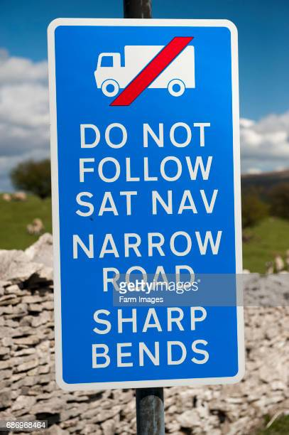 Signs on a narrow road warning wagons against following their SatNav systems Cumbria UK