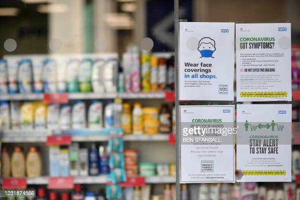 Signs on the door of a shop alert customers that due to Covid-19 face coverings are mandatory and that social distancing must be observed, in central...