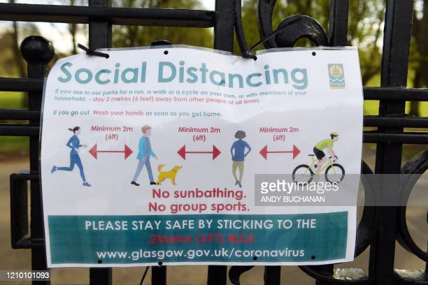 Signs on the gates advise people of social distancing rules in Queen's Park in Glasgow on April 16 2020 as Britain continues to enforce a nationwide...