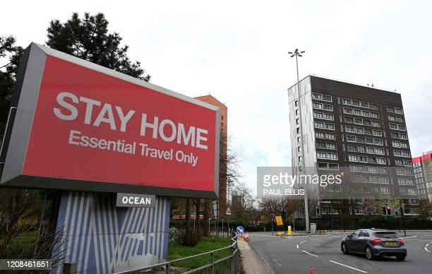 """Signs on the side of a road alert motorists to """"Stay Home"""" and that they should only travel if it is """"Essential"""", in Manchester, northern England on..."""
