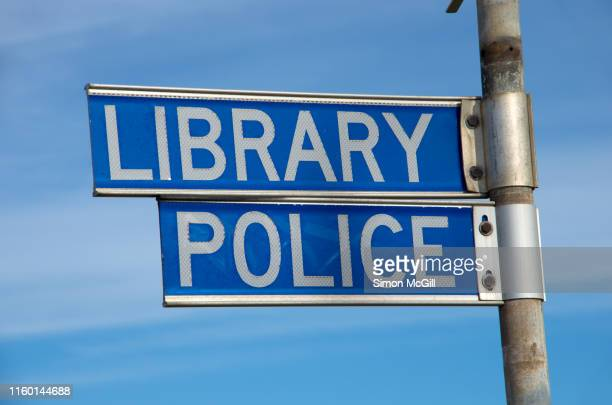 signs pointing to the local library and police station - book burning stock pictures, royalty-free photos & images