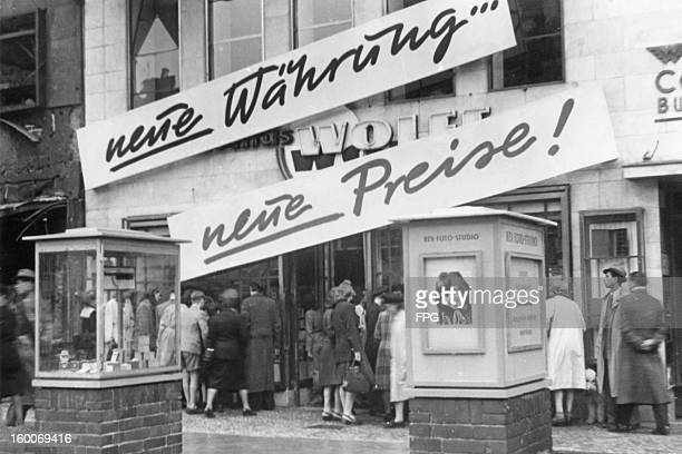 Signs reading 'Neue Währung' and 'Neue Preise' outside a Berlin department store July 1948 Store prices have dropped as a result of postwar currency...